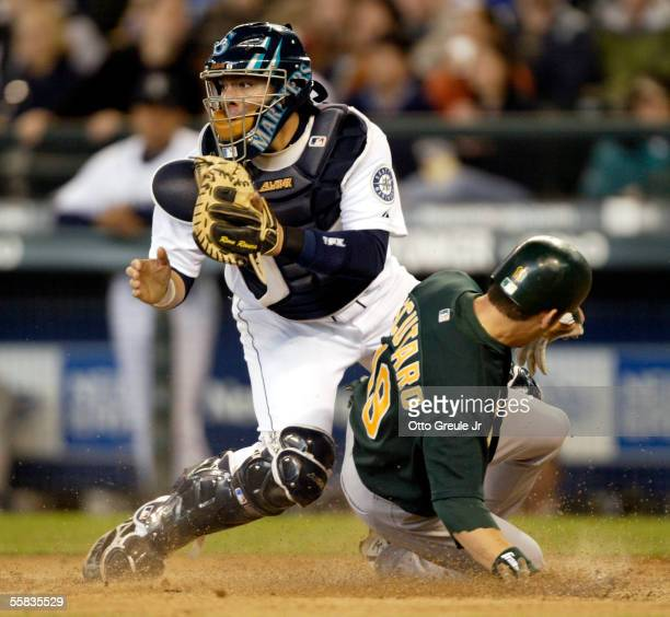Marco Scutaro of the Oakland A's scores against catcher Rene Rivera of the Seattle Mariners in the seventh inning on October 1 2005 at Safeco Field...