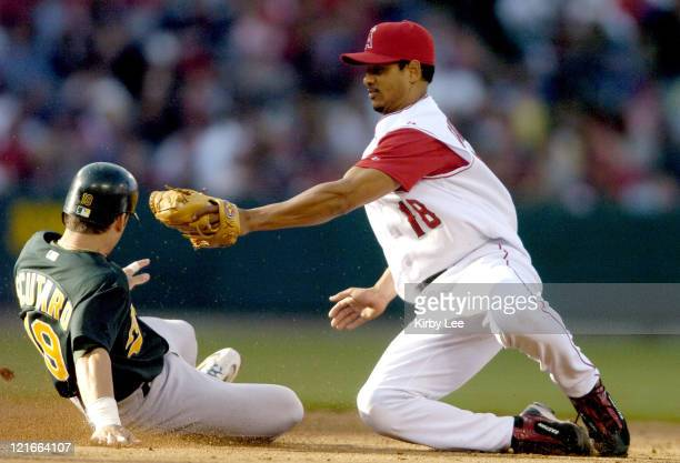 Marco Scutaro of the Oakland Athletics slides beneath the tag of Orlando Cabrera of the Los Angeles Angels of Anaheim safety into second for a stolen...