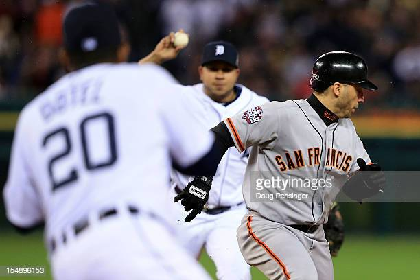 Marco Scutaro of the San Francisco Giants gets caught in a rundown against Octavio Dotel of the Detroit Tigers and Jhonny Peralta in the eighth...