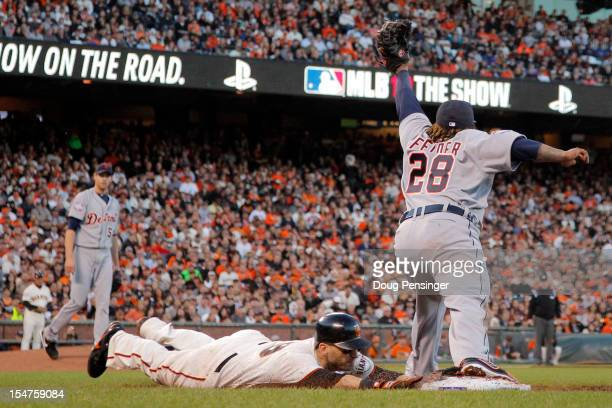 Marco Scutaro of the San Francisco Giants head first slides as he is forced out at first base by Prince Fielder of the Detroit Tigers in the third...