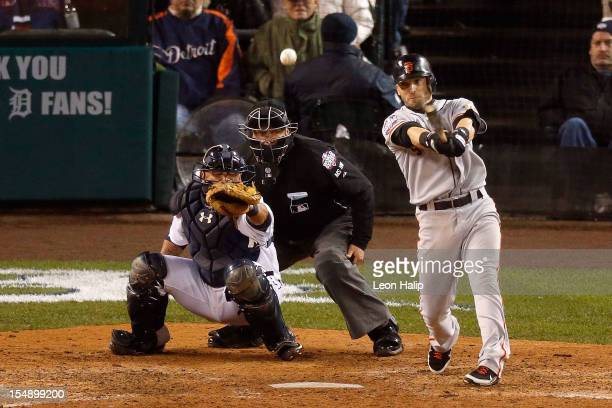 Marco Scutaro of the San Francisco Giants hits an RBI single against Phil Coke of the Detroit Tigers in the tenth inning during Game Four of the...