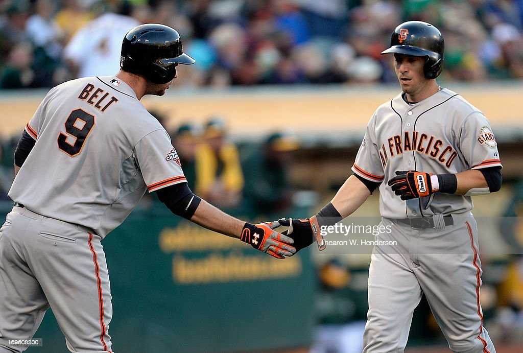 Marco Scutaro #19 of the San Francisco Giants is congratulated by Brandon Belt after Scutaro scored on an RBI single from Hunter Pence #8 (not pictured) during the first inning against the Oakland Athletics at O.co Coliseum on May 28, 2013 in Oakland, California.