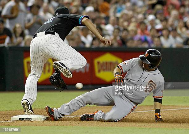 Marco Scutaro of the San Francisco Giants slides into third base with a triple as Eric Chavez of the Arizona Diamondbacks tries to field the throw...