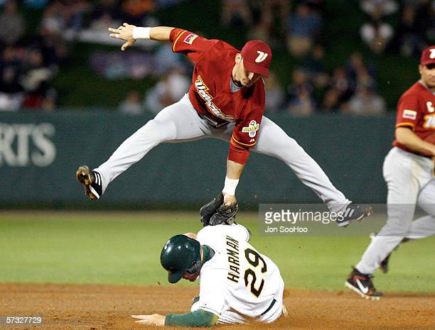 Marco Scutaro of Venezuala leaps as Bradley Harman of Australia slides during the game on Thursday March 9 2006 at Disney's Wide World of Sports...