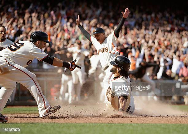 Marco Scutaro points to Angel Pagan as Pagen of the San Francisco Giants slides in to home plate for a walkoff insidethepark home run to beat the...