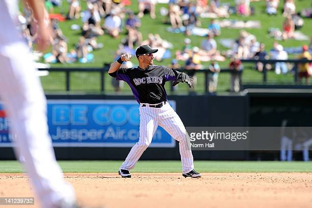 Marco Scutaro the Colorado Rockies throws the ball to first base against the Oakland Athletics at Salt River Fields at Talking Stick on March 9 2012...