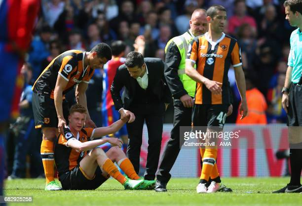 Marco Silva Manager / head coach of Hull City and Curtis Davies of Hull City pick a dejected Sam Clucas of Hull City off the pitch during the Premier...