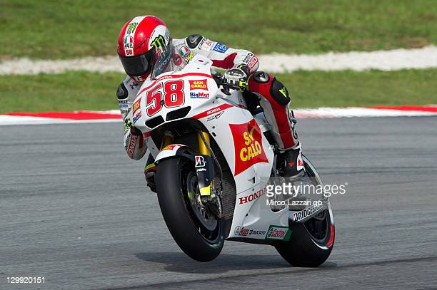 Marco Simoncelli of Italy and San Carlo Honda Gresini lifts the front wheel during the qualifying practice of MotoGP of Malaysia at Sepang Circuit on...