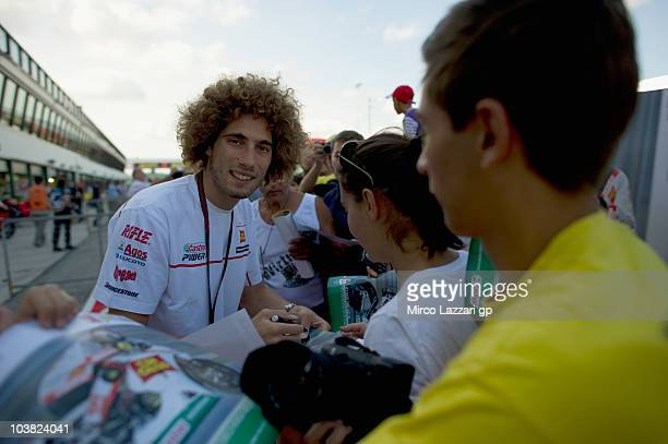 Marco Simoncelli of Italy and San Carlo Honda Gresini signs autographs for fans during the pit walk of MotoGP of San Marino in Misano World Circuit...