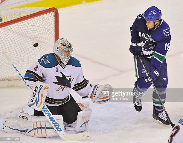 Marco Sturm of the Vancouver Canucks watches the puck fly past Goaltender Thomas Greiss of the San Jose Sharks and into the goal during their game at...