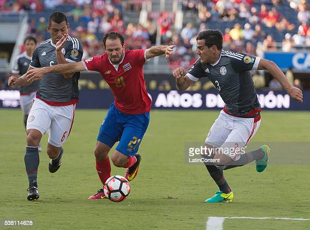 Marco Urena of Costa Rica is challenged by Miguel Samudio and Gustavo Gomes of Paraguay in the group A match between Costa Rica and Paraguay at...