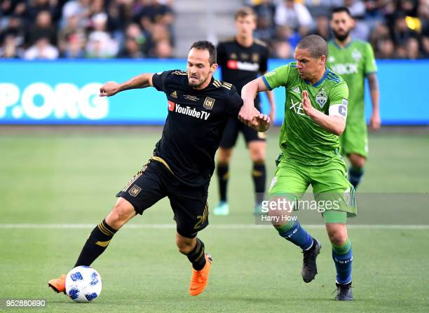 Marco Urena of Los Angeles FC is chased by Osvaldo Alonso of Seattle Sounders during the first half of the inaugural home game at Banc of California...