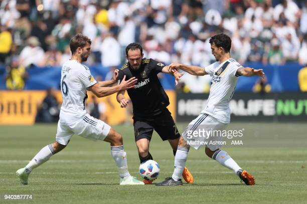 Marco Urena of Los Angeles FC / LAFC gets past Jorgen Skjelvik and Servando Carrasco of Los Angeles Galaxy during the MLS match between Los Angeles...