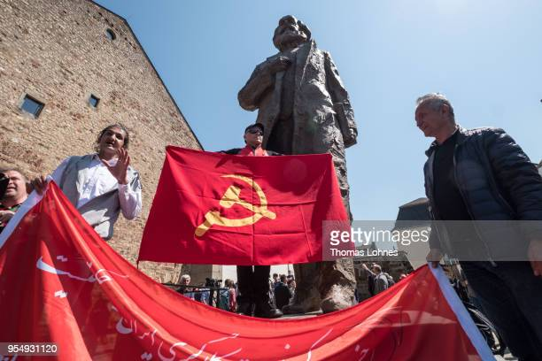 Marco Urquieta visitor of Bolivia stands with a communistic flag in front of the sculpture of German philosopher and revolutionary Karl Marx after...