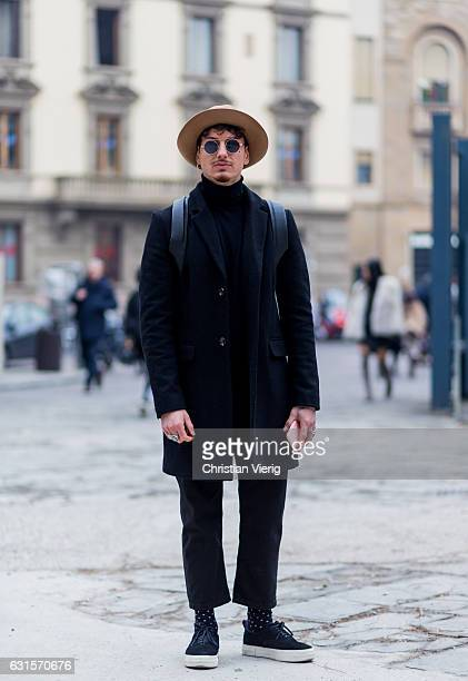 Marco Valerio Lelli is wearing a hat, black wool coat, cropped pants on January 12, 2017 in Florence, Italy.