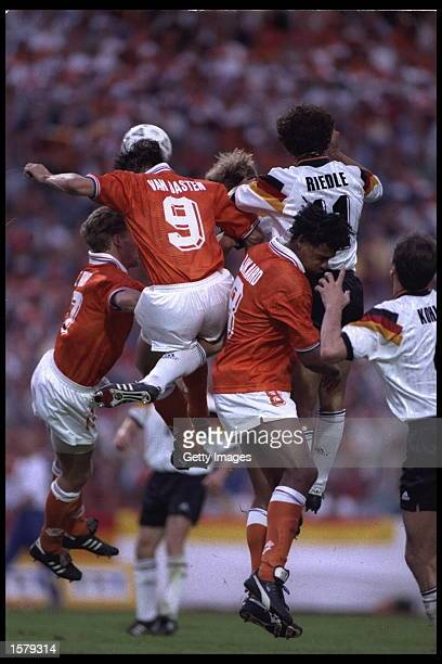 Marco Van Basten of Holland wins the header as he is challenged by his teammate Frank Rikyaard#8 and Germany's Karl Heinz Riedle#11 during the...