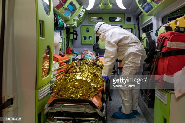 Marco Vangelista, crew member of an ambulance of the Italian Red Cross attend to a patient positive to COVID-19 during an emergency intervention on...