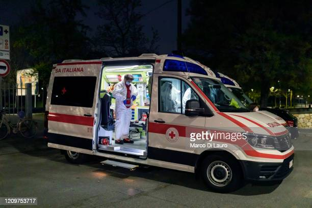 Marco Vangelista, crew member of an ambulance of the Italian Red Cross, puts on the protective suit before an emergency intervention on a patient...