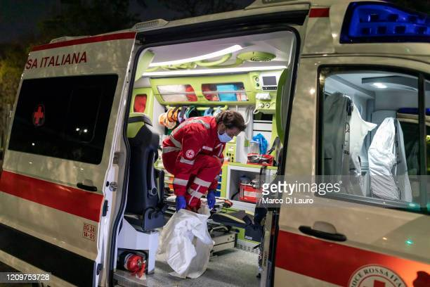 Marco Vangelista crew member of an ambulance of the Italian Red Cross puts on the protective suit before an emergency intervention on a patient...
