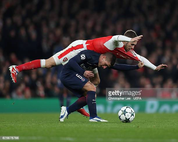 Marco Verratti of PSG is below Aaron Ramsey of Arsenal as they battle for the ball during the UEFA Champions League match between Arsenal FC and...