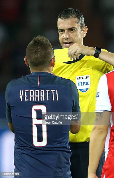 Marco Verratti of PSG receives a yellow card from referee Viktor Kassai of Hungary during the UEFA Champions League group phase match between Paris...