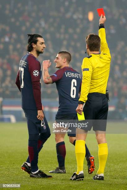 Marco Verratti of PSG receives from referee Felix Brych of Germany his second yellow card and is sent off while Javier Pastore of PSG looks on during...