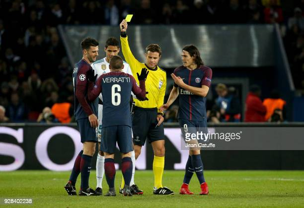 Marco Verratti of PSG receives his first yellow card by referee Felix Brych of Germany while Thiago Motta of PSG Raphael Varane of Real Madrid...