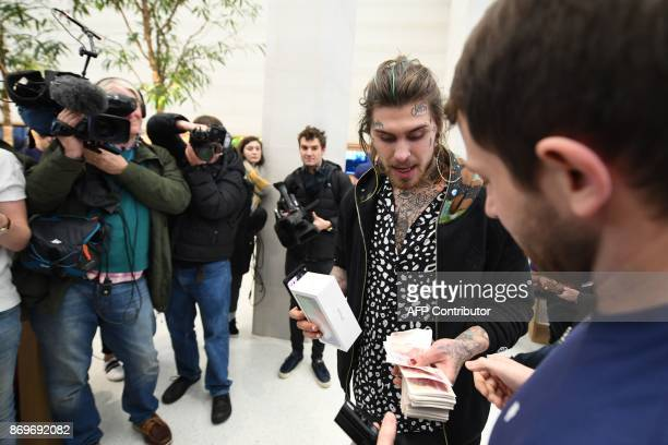 Marco White Jr son of British chef Marco Pierre White pays cash for his Apple iPhone X after being the first to enter to buy the newly released...