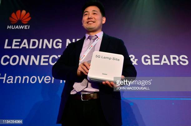 Marco Xu Digital Indoor Solution Director of Chinese telecom giant Huawei presents the 5G Lamp Site basis station during a press conference at the...