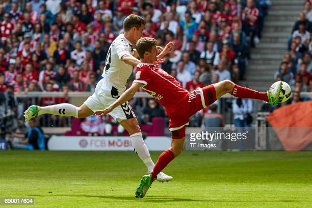 MarcOliver Kempf of Freiburg and Thomas Mueller of Bayern Muenchen battle for the ball during the Bundesliga match between Bayern Muenchen and SC...