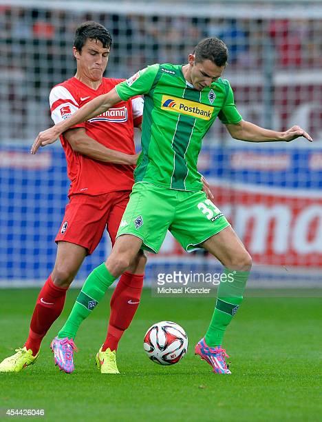 Marc-Oliver Kempf of Freiburg challenges Branimir Hrgota of Borussia Moenchengladbach during the Bundesliga match between SC Freiburg and Borussia...