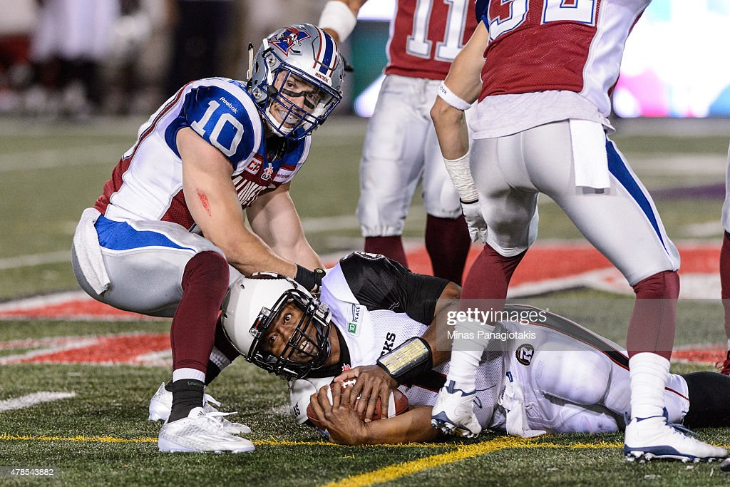 Marc-Olivier Brouillette #10 of the Montreal Alouettes holds down Henry Burris #1 of the Ottawa Redblacks during the CFL game at Percival Molson Stadium on June 25, 2015 in Montreal, Quebec, Canada. The Ottawa Redblacks defeated the Montreal Alouettes 20-16.