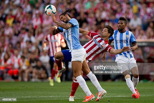 Marcos A Angeleri of Malaga CF wins the header after Diego Ribas of Atletico de Madrid during the La Liga match between Club Atletico de Madrid and...