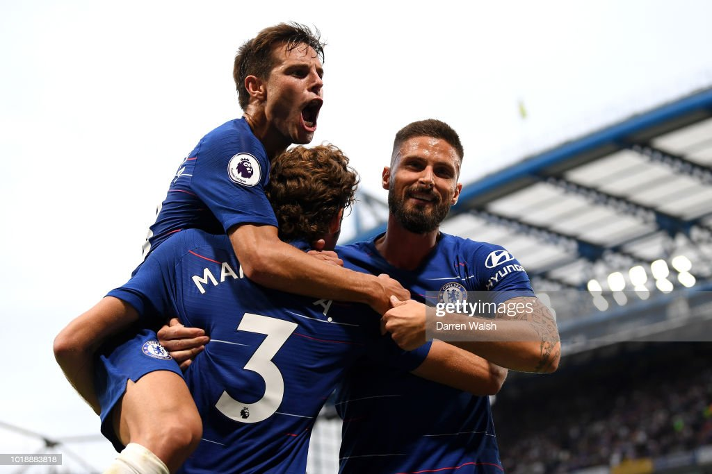 Marcos Alonso of Chelsea celebrates after scoring his team's third goal with team mates Cesar Azpilicueta and Olivier Giroud during the Premier League match between Chelsea FC and Arsenal FC at Stamford Bridge on August 18, 2018 in London, United Kingdom.