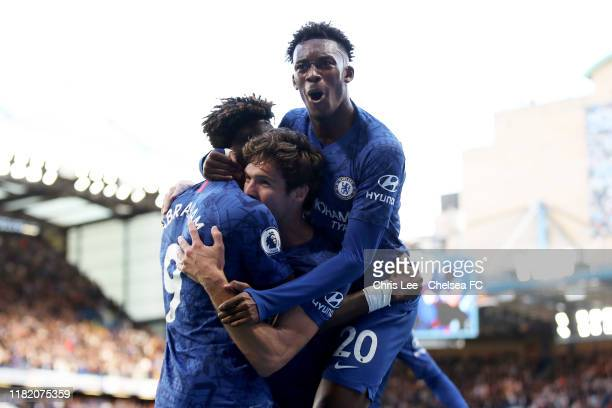 Marcos Alonso of Chelsea celebrates with teammate Tammy Abraham as Callum Hudson-Odoi jumps on top after scoring his team's first goal during the...