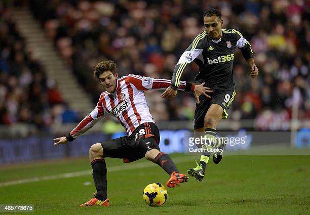 Marcos Alonso of Sunderland is tackled by Peter Odemwingie of Stoke City during the Premier League match between Sunderland and Stoke City at Stadium...
