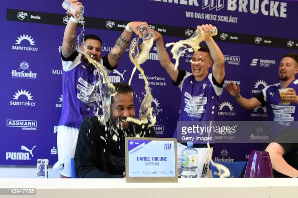 Marcos Alvarez and Thomas Konrad of Osnabrueck celebrate their teams promotion to the 2 Bundesliga with head coach Daniel Thioune after winning the 3...