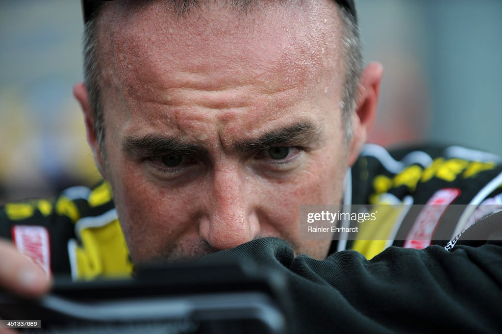 Marcos Ambrose, driver of the #9 Black & Decker Ford, stands on the grid during qualifying for the NASCAR Sprint Cup Series Quaker State 400 presented by Advance Auto Parts at Kentucky Speedway on June 27, 2014 in Sparta, Kentucky.