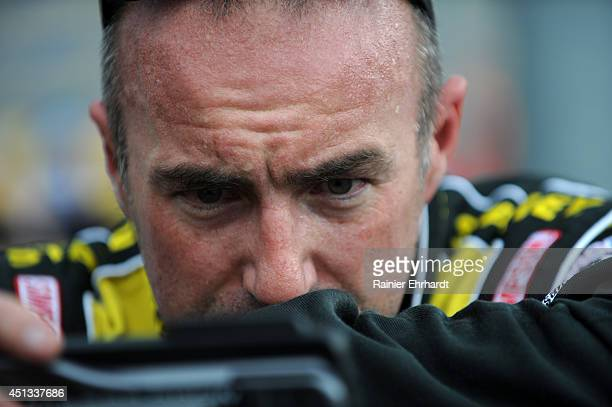Marcos Ambrose, driver of the Black & Decker Ford, stands on the grid during qualifying for the NASCAR Sprint Cup Series Quaker State 400 presented...