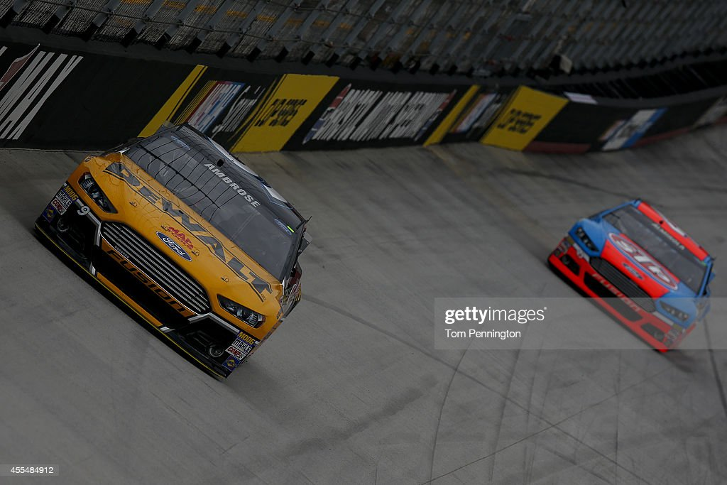 Marcos Ambrose, driver of the #9 DeWalt Ford, leads Aric Almirola, driver of the #43 STP Ford, during practice for the NASCAR Sprint Cup Series Irwin Tools Night Race at Bristol Motor Speedway on August 22, 2014 in Bristol, Tennessee.