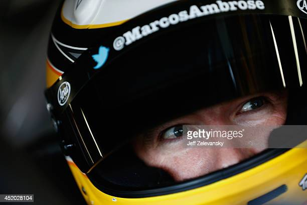 Marcos Ambrose, driver of the DeWalt Ford, sits in his car in the garage area during practice for the NASCAR Sprint Cup Series Camping World RV Sales...