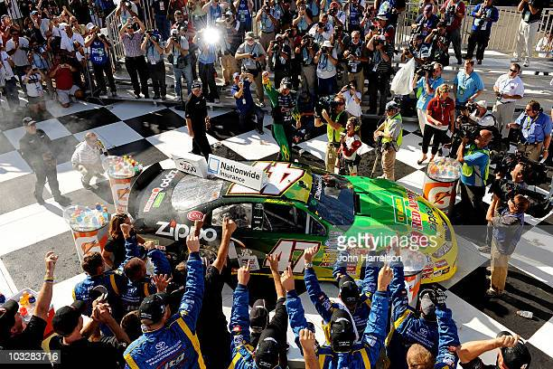 Marcos Ambrose, driver of the Kwik Fil/Zippo Chevrolet, celebrates in victory lane after winning the NASCAR Nationwide Series Zippo 200 at Watkins...