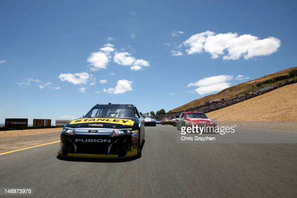 Marcos Ambrose, driver of the Stanley Ford, and Jeff Gordon, driver of the Drive to End Hunger Chevrolet, lead the field in the pace laps prior to...