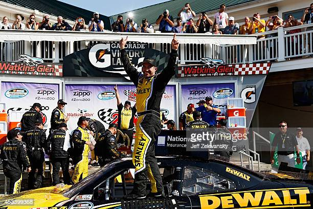 Marcos Ambrose, driver of the Stanley Ford, celebrates in Victory Lane after winning the NASCAR Nationwide Zippo 200 at Watkins Glen International on...