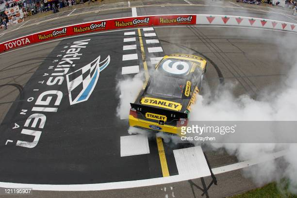 Marcos Ambrose, driver of the Stanley Ford, celebrates with a burnout after winning the NASCAR Sprint Cup Series Heluva Good! Sour Cream Dips at the...