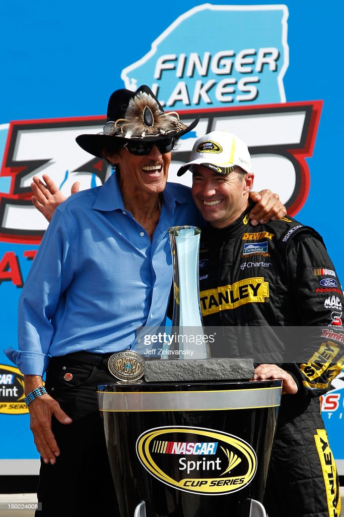 Marcos Ambrose, driver of the #9 Stanley Ford, celebrates with team owner Richard Petty in Victory Lane after winning the NASCAR Sprint Cup Series Finger Lakes 355 at the Glen at Watkins Glen International on August 12, 2012 in Watkins Glen, New York.