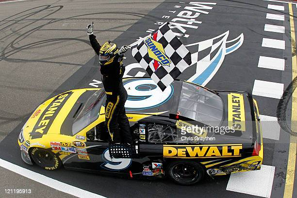 Marcos Ambrose, driver of the Stanley Ford, celebrates with the checkered flag after winning the NASCAR Sprint Cup Series Heluva Good! Sour Cream...