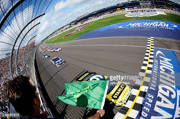 Marcos Ambrose, driver of the Stanley Ford, leads the field to the green flag to start the NASCAR Sprint Cup Series Quicken Loans 400 at Michigan...