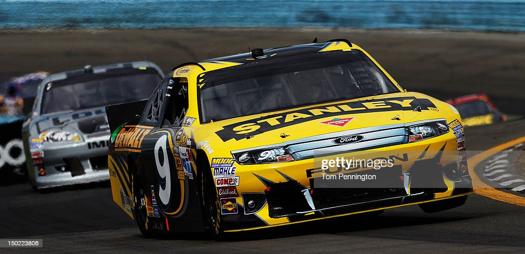 Marcos Ambrose, driver of the #9 Stanley Ford, races ahead of Jimmie Johnson, driver of the #48 Lowe's Cortez Silver Chevrolet, during the NASCAR Sprint Cup Series Finger Lakes 355 at the Glen at Watkins Glen International on August 12, 2012 in Watkins Glen, New York.