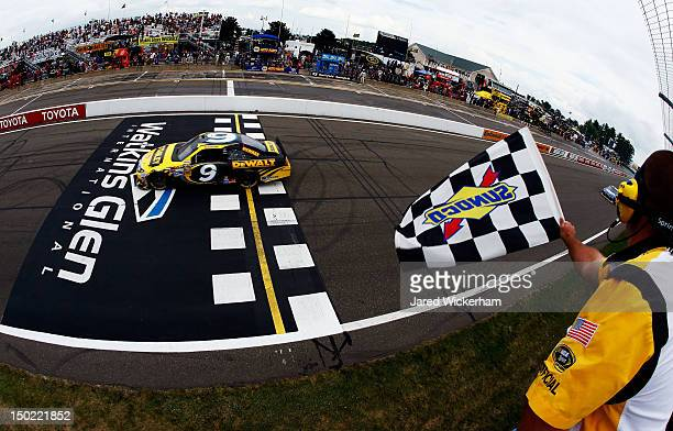 Marcos Ambrose, driver of the Stanley Ford, races past the checkered flag to win the NASCAR Sprint Cup Series Finger Lakes 355 at the Glen at Watkins...